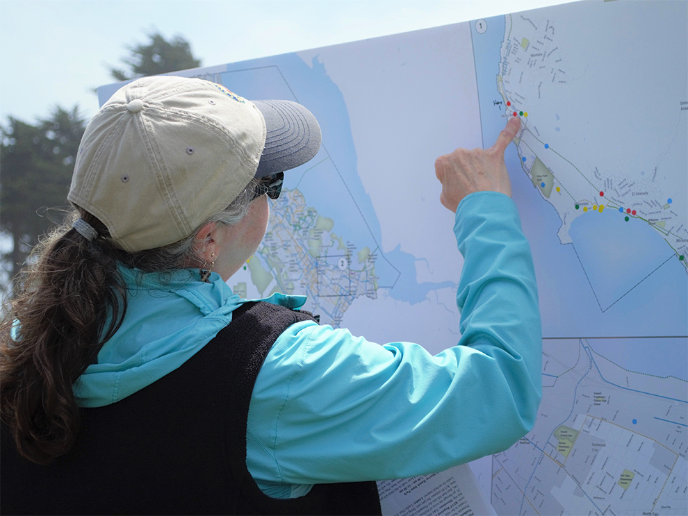 Woman points to map of Unincorporated San Mateo County to provide feedback on walking and biking.
