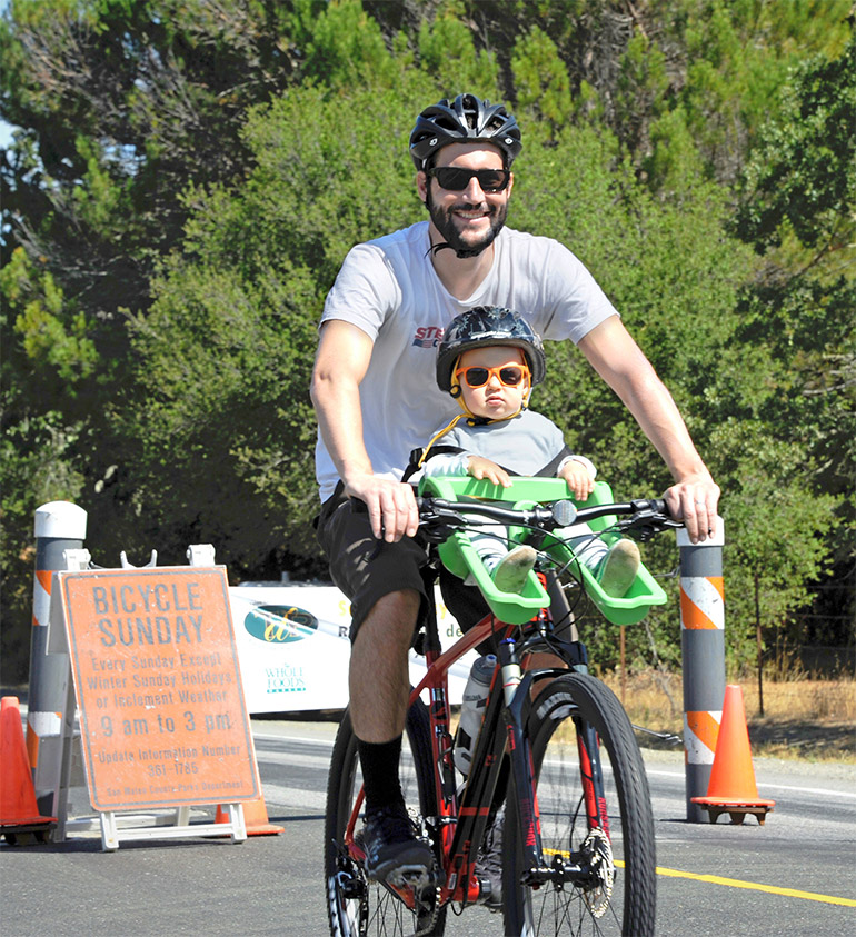 A man smiles while riding a bike with a small child strapped in the front of the bicycle in a green children's seat