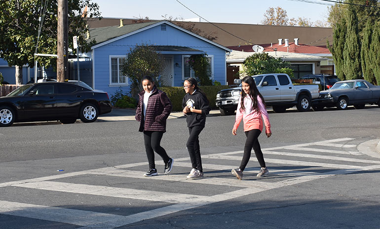 three teenagers cross the street on a crosswalk with houses and parked cars in the background.